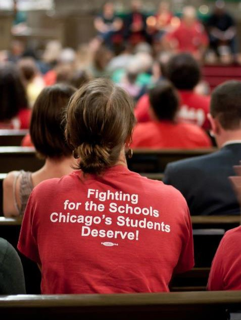 "A crowded event with a participant wearing a shirt emblazoned ""Fighting for the Schools Chicago's Students Deserve"""
