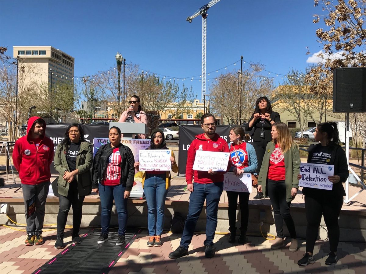 """Nine teachers, decked in union-red shirts posing with signs that say """"End All Detentions"""" and """"Amnesty Now."""""""