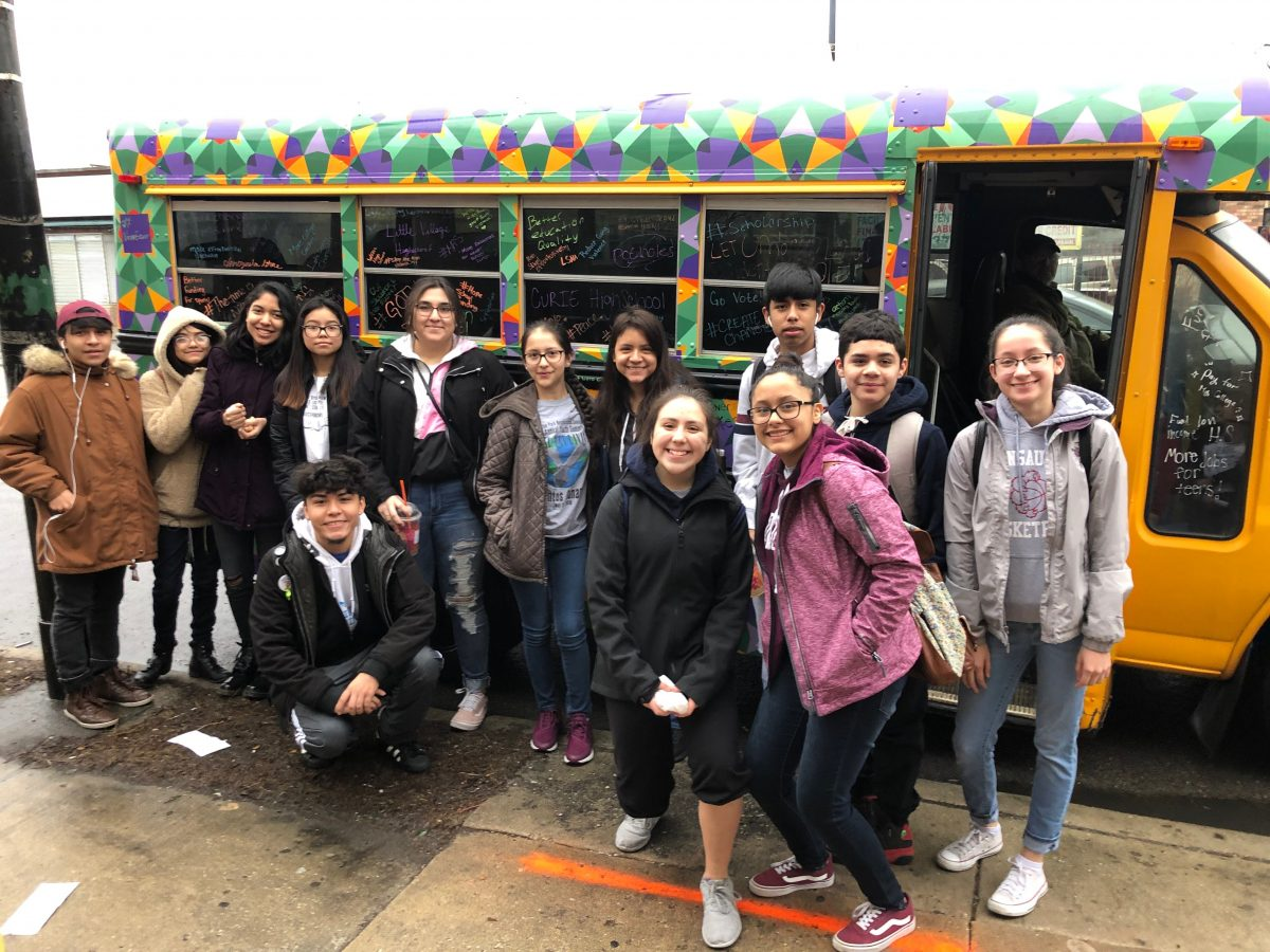 A diverse group of dozen high school students pose in front of a multi-colored bus.