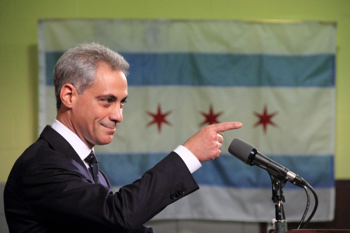Photo of Chicago mayor pointing finger in front of Chicago flag hanging on the wall.
