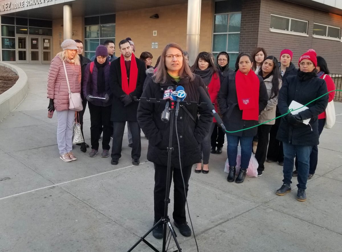 Photo of Hernandez Middle School with a group of teachers and parents in front and a female CTU official speaking at a microphone.