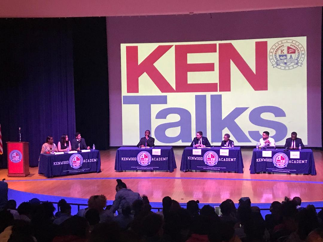 Five adults sitting at three different tables, three high schools students sitting at another table, with a large red and blue banner that says KEN Talks behind them.