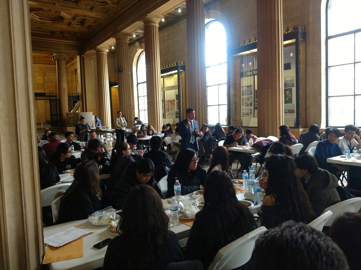 Large group of high school students, at long tables, eating lunch and listening to a speaker.