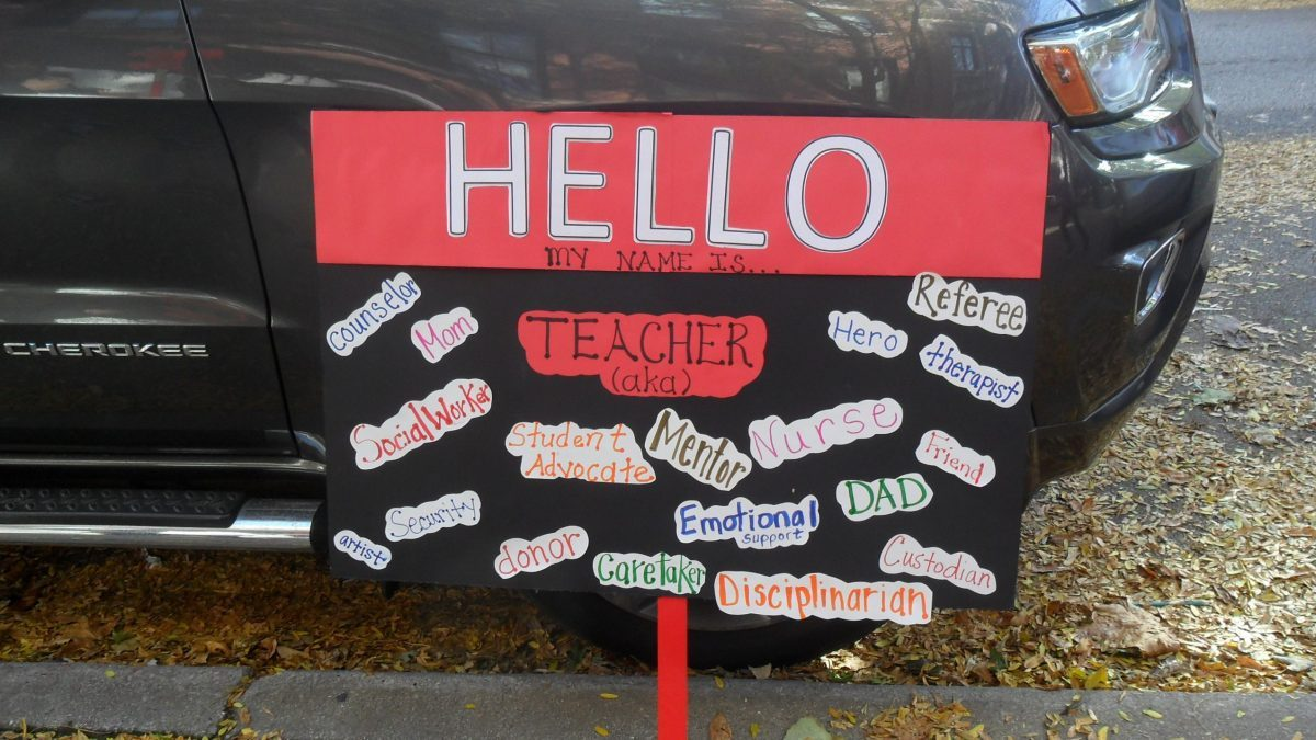 A sign mimicking a name badge lists the many roles a teacher must fill, such as caretaker, social worker, disciplinarian...