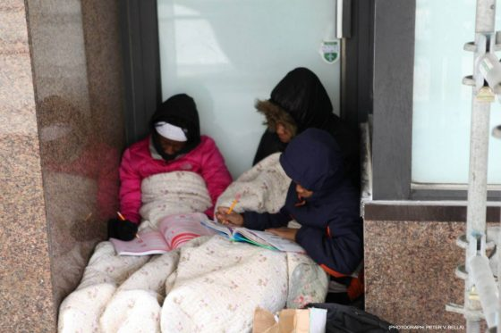 A mother shelters her children in a doorway underf a blanket as they write in workbooks.