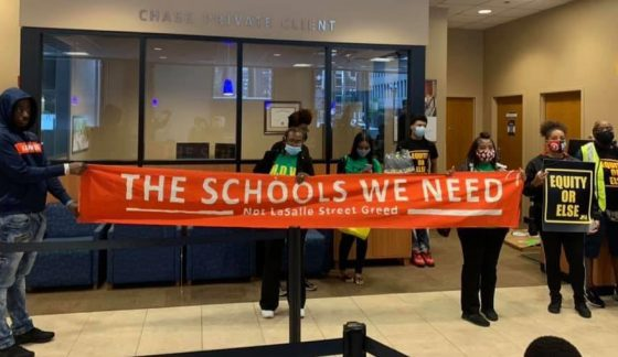 Seven young Black men and women dressed in black in the lobby of Chase Bank, holding red sign with white letters that reads: The Schools We Need and holding black and yellow posters that read: Equity or Else.