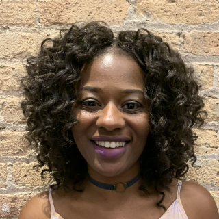 Head shot of a Black woman with mid-length curly dark hair in front of a tan brick wall.