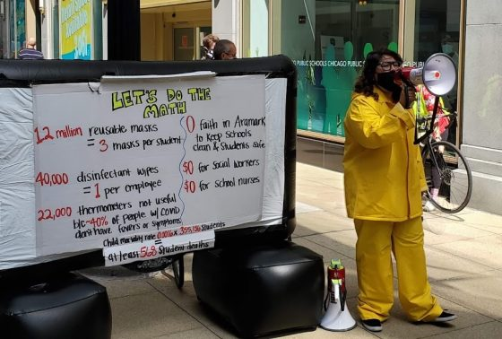 Photo from a protest outside of Chicago Public Schools HQ. A woman in a hazmat suit, holds a bull horn in front of a sign that reads: Let's do the math.