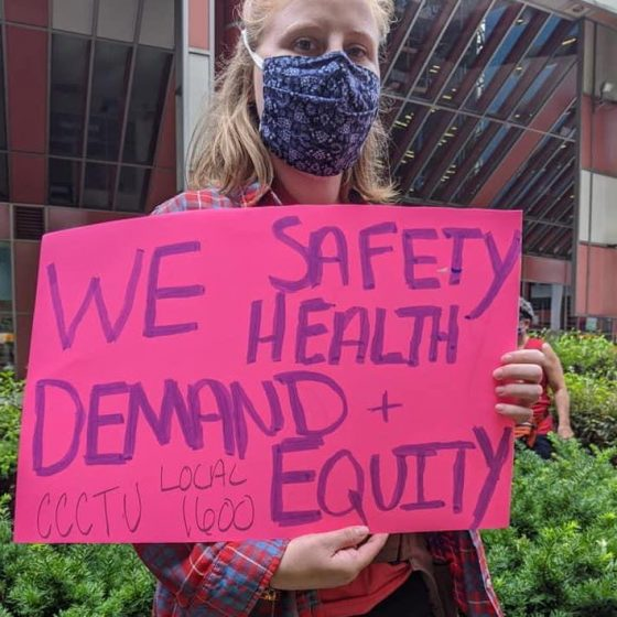 Young, blonde woman wearing a blue mask, standing in front of some green bushes, holding a pink poster that says: WE demand safety, health and equity.