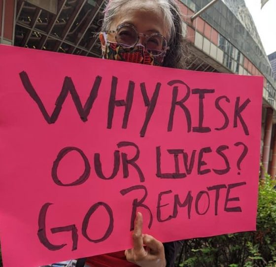 Protester holds sign: Why risk our lives? Go remote