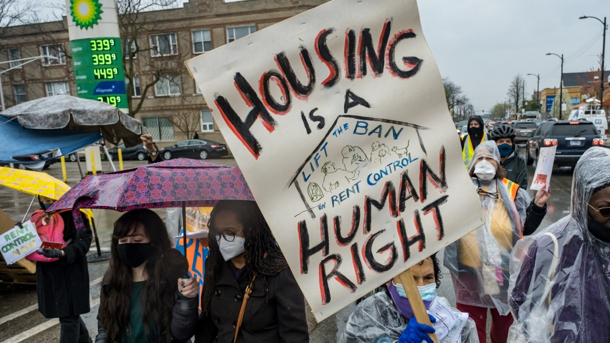 Community members march through the rain carrying signs that say: Housing is a human right and Rent contol.