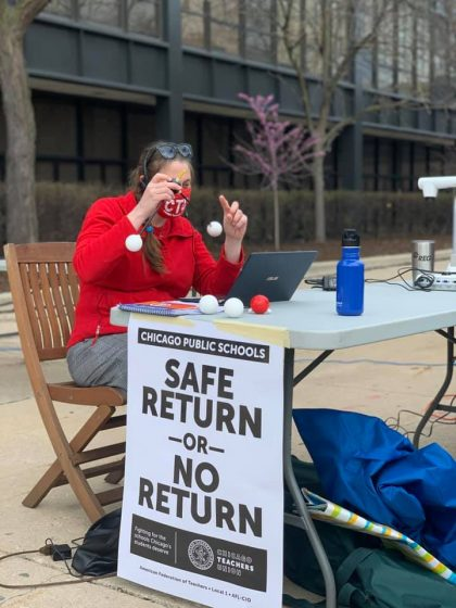 A teacher sits outside Whitney Young High School teaching remotely with a sign that says: Safe return or no return.