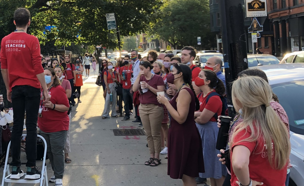 About 30 masked teachers in red gather on the sidewalk for a walk-in all listening as a teacher standing on a small stepladder exhorts the crowd.